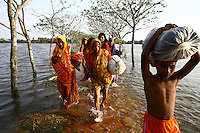 Women carry their belongings through floodwaters. Thousands of people were displaced in Shyamnagar Upazila, Satkhira district after Cyclone Aila struck Bangladesh on 25/05/2009, triggering tidal surges and floods..