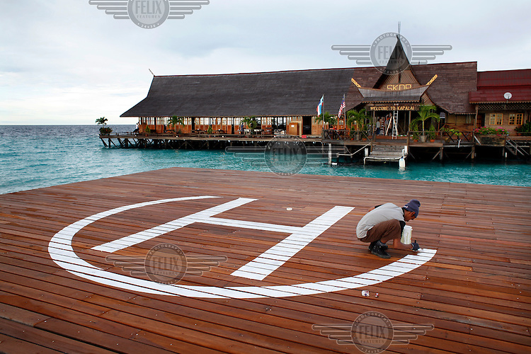 Landing pad for helicopter being painted. Used by rich guests and rescue services. Kapalai diving resort, Borneo, Malaysia.