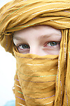 Close up portrait Caucasian young woman wearing oriental ethnic scarf around her head showing only eyes