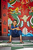 VIETNAM, Hoian, an old man wearing blue uniform, sitting outside a temple