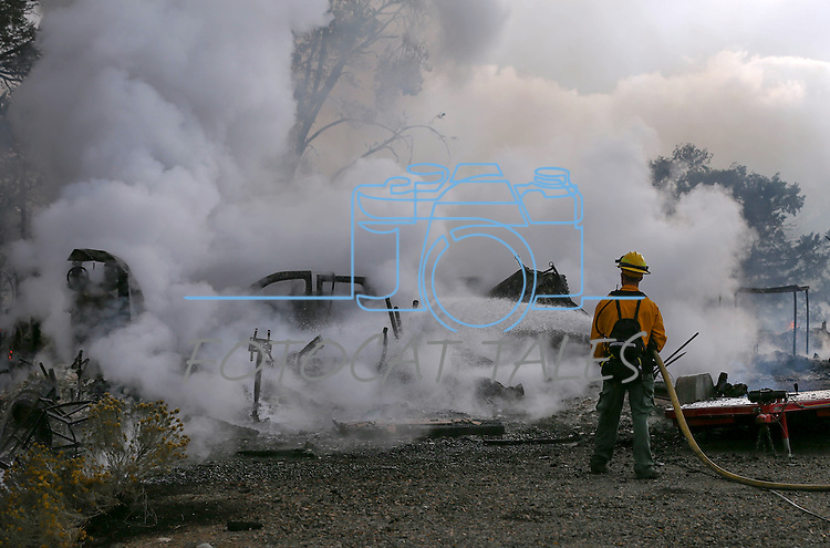Firefighters battle a brush fire near the Fish Hatchery south of Gardnerville, Nev. on Sunday, Oct. 2, 2016. Two homes and several outbuildings were destroyed in the approximately 100-acre fire driven by high winds.<br /> Photo by Cathleen Allison