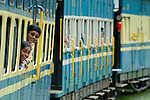 Loughing girls looking out of the train windows of the Nilgiri Mountain Railway driving from Coonoor to Ooty. Tamil Nadu, India.  --- No releases available. --- Info: The Nilgiri Mountain Railway (NMR) is the only rack railway in India and connects the town of Mettupalayam with the hill station of Udagamandalam (Ooty), in the Nilgiri Hills of southern India. The construction of the 46km long meter-gauge singletrack railway in Tamil Nadu State was first proposed in 1854, but due to the difficulty of the mountainous location, the work only started in 1891 and was completed in 1908. This railway, scaling an elevation of 326m to 2,203m and still in use today, represented the latest technology of the time. In July 2005, UNESCO added the NMR as an extension to the World Heritage Site of Darjeeling Himalayan Railway.