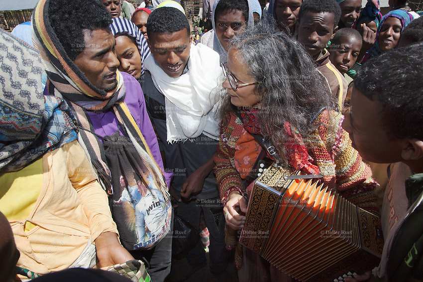 """Ethiopia. Southern Nations, Nationalities, and Peoples' Region. Bojeber Village. High altitude: 3'250 metres. Market day. Chantal Marguerie plays accordion to a group of ethiopian farmers from the Gourague tribe. Marc Vella is a french musician and a nomadic pianist. Over the last 25 years he has travelled with his Grand Piano in around forty countries to celebrate humanity. Creator of """"La Caravane amoureuse"""" (The Caravan of Love) he takes people with him to say """"I love you"""" to others and """"lovingly conquered"""" their hearts and souls. Southern Nations, Nationalities, and Peoples' Region (often abbreviated as SNNPR) is one of the nine ethnic divisions of Ethiopia. 15.11.15 © 2015 Didier Ruef"""