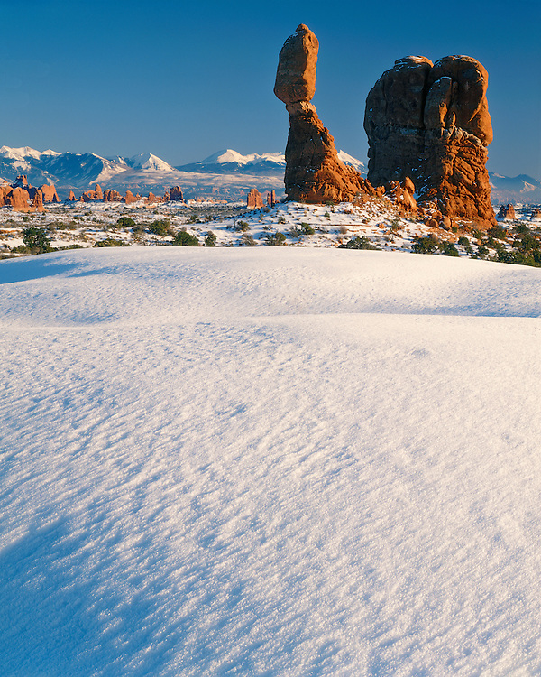 Afternoon winter light on Balanced Rock below the La Sal Mountains; Arches National Park, UT