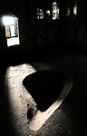 Sunlight shining into an old barn through a doorway onto a grain dip in the floor