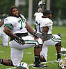 James Carpenter #77 of the New York Jets, left, stretches during the start of a day of team training camp at Atlantic Health Jets Training Center in Florham Park, NJ on Tuesday, Aug. 2, 2016.