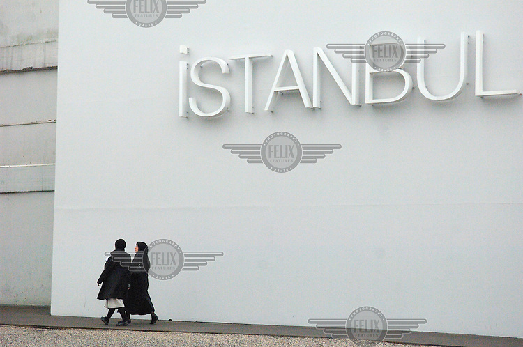 Muslim women passing beneath the sign of 'Istanbul Modern', the city's new Twentieth Century art museum housed in a former warehouse by the Bosphorus.