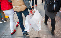 Shoppers in New York holding Uniqlo shopping bags with their various purchases on Tuesday, October 25, 2016. Consumer confidence is reported to have dropped in October attributed in part to the U.S. election. (© Richard B. Levine)