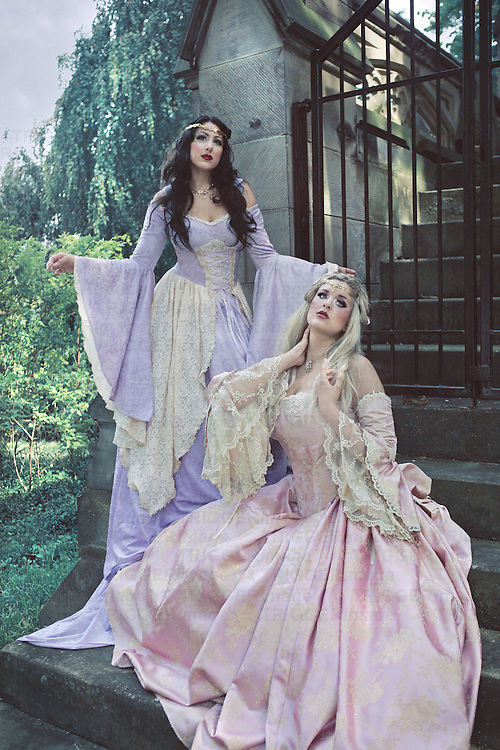 Two renaissance woman in fancy pastel costumes in front of a castle