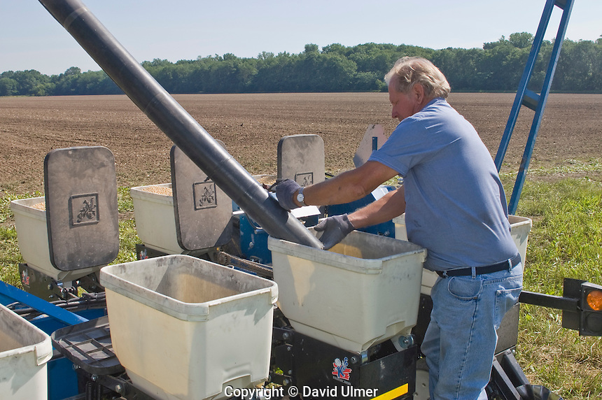 Farmer loading soybean seed hoppers on planter