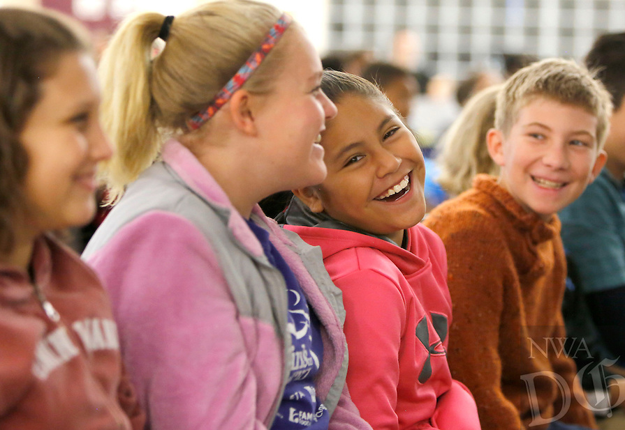 NWA Democrat-Gazette/DAVID GOTTSCHALK  Karen Vasquez (second from right) laughs at the lyrics of a song Tuesday, October 6, 2015 while listening to Joe Crookston perform on stage for the fifth grade students at Holt Middle School in Fayetteville. Crookston performed and led workshops in the area for the past week as part of the True Lit Festival.