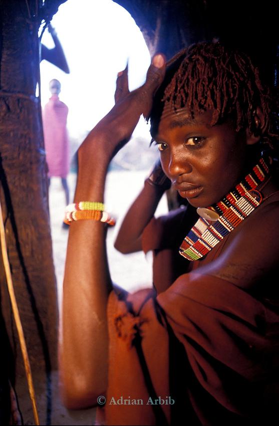 A Maasai Moran inside his hut in the Maasai Moran manyatta in Kajiado, Kenya .  He has lived here for several weeks with his age set as part of  his initiation into  manhood.