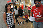 (R-L) Edison Onate, 48, of Chicago, Illinois holds up his shopping list for his children's back to school shopping as his daughter Alexis Onate, 12, looks on and son (in background looking at store window) Edison Onate, Jr., 12 of Bloomington, Illinois at the Woodfield Mall in Schaumburg, Illinois on September 5, 2010.