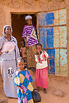 "A friendly group of women and children greet me as I walk through the town of Torodi in southwestern Niger. They stand in front of their handmade mud-brick house. Each year, an extra coating of mud is smeared on the outside walls to keep the rain from washing the bricks away and the house from falling. The roof of the house is a thin sheet of aluminum held up by cylindrical wood beams collected in the ""bush."""