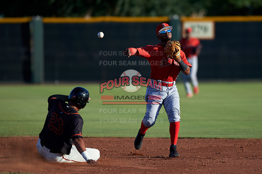 AZL Angels second baseman Kendy Moya (3) turns a double play in front of Bryan Hernandez (23) during an Arizona League game against the AZL Giants Black at the Giants Baseball Complex on June 21, 2019 in Scottsdale, Arizona. AZL Angels defeated AZL Giants Black 6-3. (Zachary Lucy/Four Seam Images)
