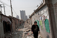 An elderly woman walks through a torn down alleyway at Dawangjing Village which is being demolished on April 9, 2009 on the outskirts of Beijing, China. The local authorities are evicting residents, who are mainly migrant workers, to redevelop the area. The redevelopment of Beijing continues in high speed.
