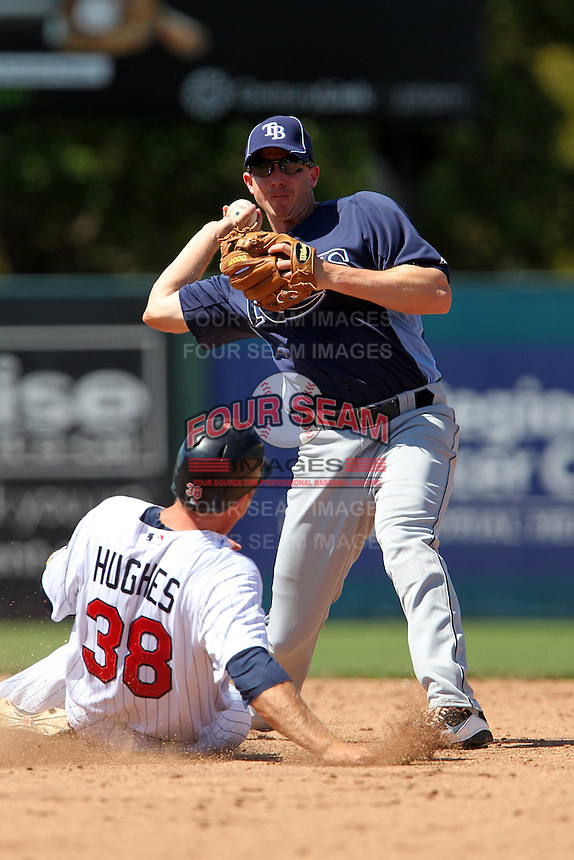 Tampa Bay Rays second baseman Elliot Johnson #9 attempts to turn a double play as Luke Hughes #38 slides in during a spring training game against the Minnesota Twins at Hammond Stadium on March 26, 2012 in Fort Myers, Florida.  The Rays defeated the Twins 10-4.  (Mike Janes/Four Seam Images)