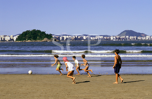 Santos, Sao Paulo State, Brazil. Boys playing football on the beach with high-rise buildings behind.