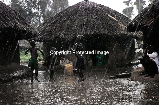 LALIYA, UGANDA MAY 26: Children play outside huts in a heavy rainfall on May 26, 2005 in Laliya, a poor rural village in northern Uganda. Many children in this area are afraid of being abducted by the Lord's Resistance Army (LRA). The rebel group has brought terror to Northern Uganda for almost twenty years, fighting the Ugandan government. The victims are usually children, which are abducted and used as child soldiers and sex slaves. About 1.5 million people have fled villages and live in about 180 squalid Internally Displaced People (IDP) camps, which has changed the rural life in Northern Uganda. About 20,000 children walk every day to the nearby provincial capital Gulu where NGO:s house the children. Many children are too afraid to sleep in the villages. (Photo: Per-Anders Pettersson)