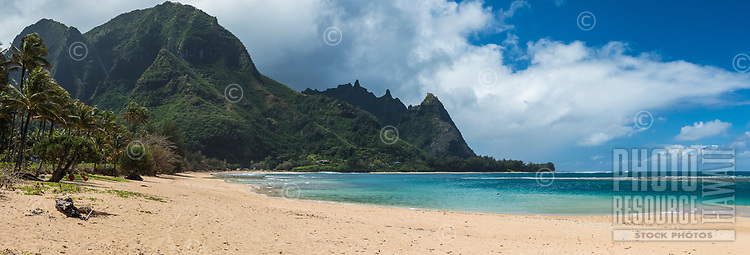 A panorama of the beach, mountains including Mount Makana and the clear waters at Tunnels Beach on the north shore of Kaua'i.