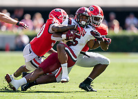 ATHENS, GA - OCTOBER 12: Rico Dowdle #5 of the South Carolina Gamecocks is tackled by Tae Crowder #30 and Monty Rice #32 of the Georgia Bulldogs during a game between University of South Carolina Gamecocks and University of Georgia Bulldogs at Sanford Stadium on October 12, 2019 in Athens, Georgia.