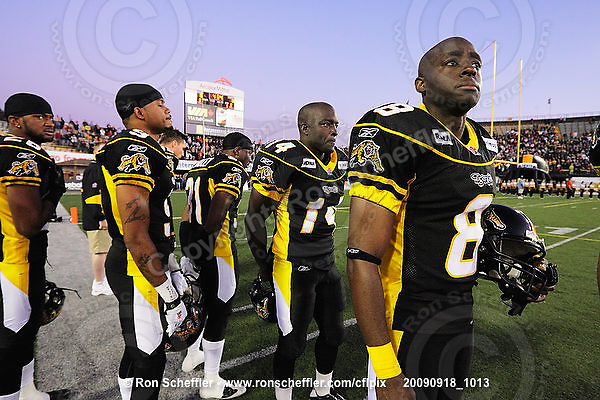 September 18, 2009; Hamilton, ON, CAN; Hamilton Tiger-Cats defensive back Chris Thompson (26), defensive back Geoff Tisdale (9), running back DeAndra' Cobb (14) and wide receiver Corey Grant (8) during the singing of the national anthem. CFL football: Calgary Stampeders vs. Hamilton Tiger-Cats at Ivor Wynne Stadium. The Tiger-Cats defeated the Stampeders 24-17. Mandatory Credit: Ron Scheffler. Copyright (c) 2009 Ron Scheffler.