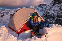 Female hiker relaxes in tent in evening sun on narrow mountain ridge at Ågskaret, Moskenesøy, Lofoten Islands, Norway