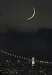 The crescent moon setting behind Oakland Bay Bridge as seen from Alameda, CA.