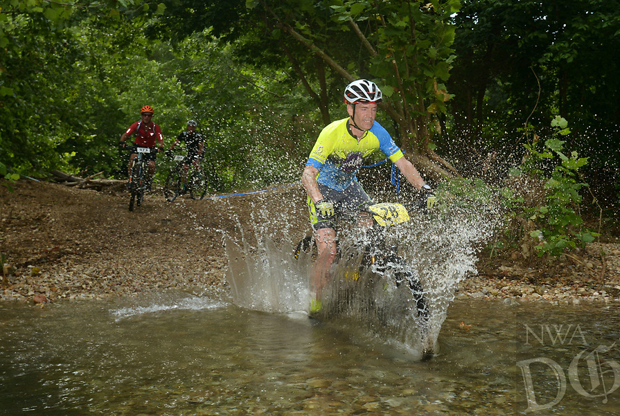 NWA Democrat-Gazette/BEN GOFF @NWABENGOFF<br /> Kirk Grynwald, a category 1 racer from Little Rock, fords a creek Sunday, July 16, 2017, during cross country races on the final day of the 19th annual Fat Tire Festival at Lake Leatherwood City Park in Eureka Springs.