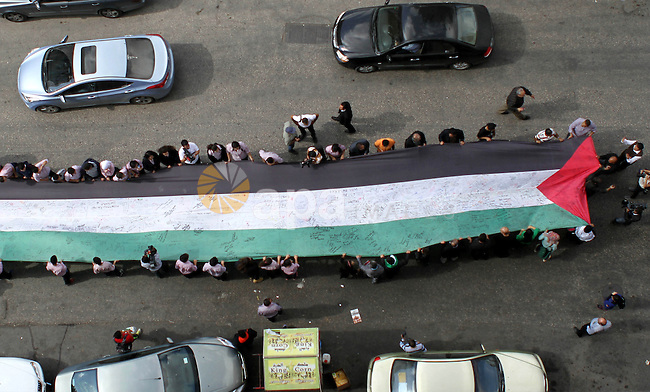 """People march as they hold a large Palestinian flag during an attempt to break the Guinness World Record for the """"largest Palestinian flag"""", in the West Bank city of Ramallah October 28, 2014. Photo by Shadi Hatem"""