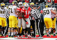Ohio State Buckeyes safety Tyvis Powell (23) holds back linebacker Curtis Grant (14) after Michigan Wolverines running back Drake Johnson (20) scored a touchdown during the 3rd quarter of the NCAA football game at Ohio Stadium on Nov. 29, 2014. (Adam Cairns / The Columbus Dispatch)