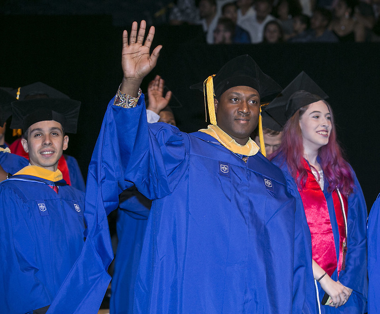 Graduates wave to their friends and family members during the DePaul University College of Computing and Digital Media and the College of Communication hold their commencement ceremony at the Allstate Arena in Rosemont, IL. (DePaul University/Jamie Moncrief)