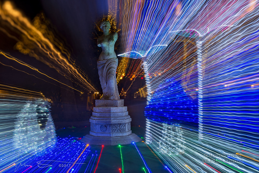 Statue with Holiday Lights, Sedona ©2017 James D Peterson.  Sedona's Tlaquepaque Arts and Crafts Village always has great holiday decorations and festivities.  This holiday display was put into warp drive by zooming my lens during a long exposure.
