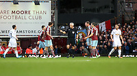 Sunday 07 December 2014<br /> Pictured: Match referee Chris Foy (C) is surrounded by West Ham players seconds before Lukasz Fabianksi of Swansea was shown the red card for his foul<br /> Re: Premier League West Ham United v Swansea City FC at Boleyn Ground, London, UK.