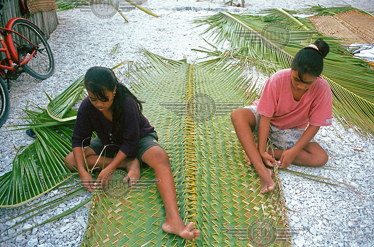 Girls making new mats out of coconut leaves in preparation for the end of term feast at Stephen Whitmee High School.