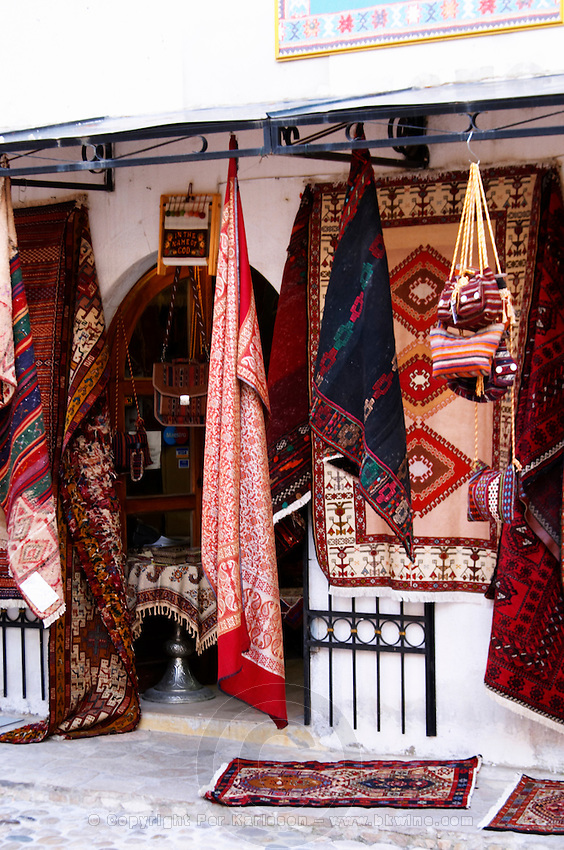 A shop selling carpets, shawls, and other craft. The busy old market bazaar street Kujundziluk with lots of tourist craft and art shops and street merchants. Historic town of Mostar. Federation Bosne i Hercegovine. Bosnia Herzegovina, Europe.