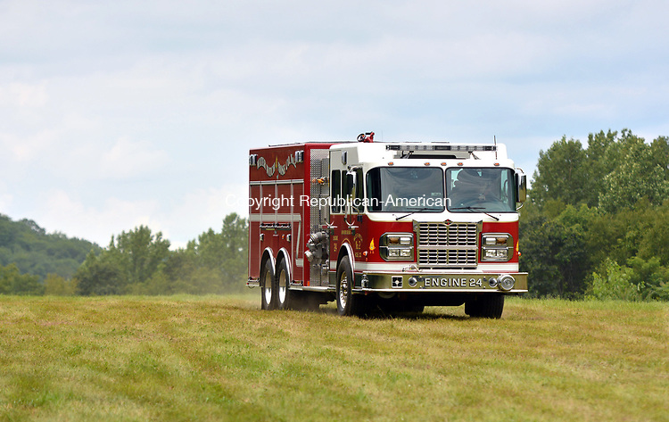 NEW MILFORD, CT-081117JS01-- Engine 24 from Water Witch Hose Co. No. 2 in New Milford leaves the scene of a fatal plan crash Friday at at Candlelight Farms Airport in New Milford. Three people were on the plane when it crashed, killing the instructor and seriously injuring a second person. <br /> Jim Shannon Republican-American