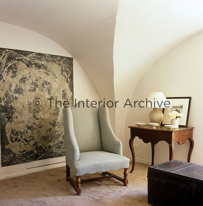 A pale blue wing-backed chair and a large painting in a corner of the living room