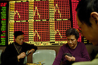 Chinese investors play cards in front of an electronic board at the stock exchange in Beijing, China. A weaker dollar in global markets coupled with calls from the US Treasury for faster China exchange rate reforms pushed the yuan to a fresh high against the US dollar recently..01 Feb 2007