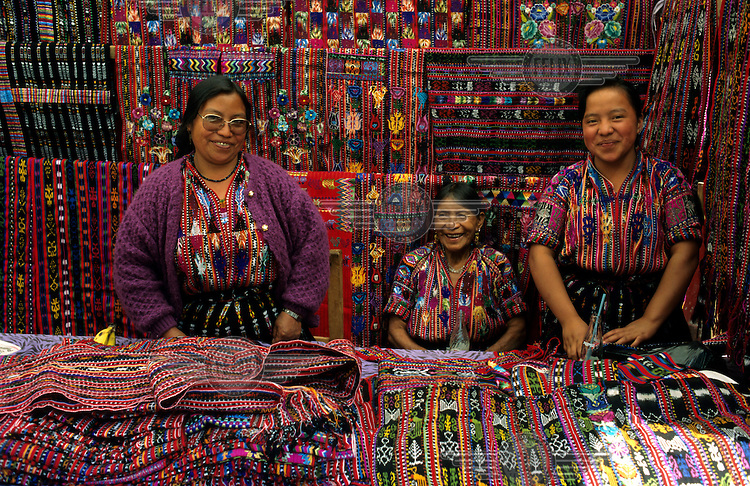 Maya women selling textiles at the Thursday market. The women are wearing huipil (traditional woven and embroidered cotton blouses) that are designed according to their village traditions.