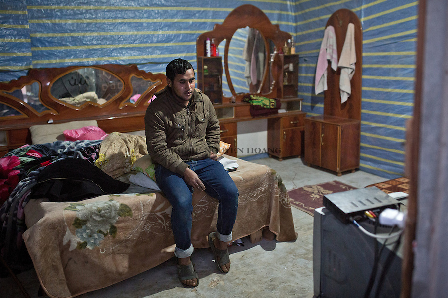 GAZA, Erez: Hassan watches television in his modest house that he shares with his wife. In a few months it will be  father for the first time at the age of 19 . After work, Hassan drinks tea with his family , watch TV when there is electricity but it is very rare that he goes outside the home soil or in Gaza City.<br /> <br /> GAZA, Erez: Hassan regarde la t&eacute;l&eacute;vision dans sa modeste chambre qu'il partage avec sa femme. Dans quelques mois, il sera papa pour la premi&egrave;re fois &agrave; l'age de 19 ans. Apr&egrave;s le travail, Hassan boit du th&eacute; avec sa famille, regarde la TV lorsqu'il y a de l'&eacute;lectricit&eacute; mais il est tr&egrave;s rare qu'il sorte en dehors du terreau familial et &agrave; Gaza City.