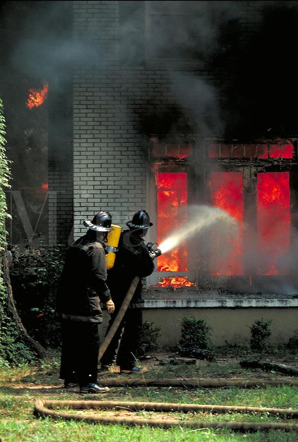 Firefighters fighting house fire. firemen. Tuscaloosa Alabama United States.
