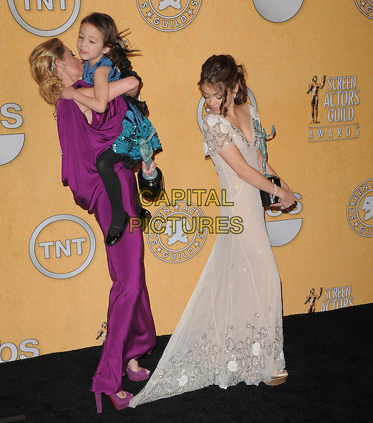 Aubrey Anderson-Emmons, Julie Bowen, Sarah Hyland  .The 18th Annual Screen Actors Guild Awards held at The Shrine Auditorium in Los Angeles, California, USA..January 29th, 2012 .SAG SAGS full length dress award trophy winner stepping standing on train funny side looking over silk satin white blue carrying holding kid child profile .CAP/RKE/DVS.©DVS/RockinExposures/Capital Pictures.