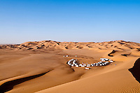 The semi-circular arrangement of the tents of the Ubari Magic Lodge camp look tiny against the vast expanse of the desert