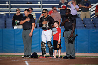 "Batavia Muckdogs catcher Igor Baez (29) stands with umpires Jordan Sandberg (left), James Jean (right), and a ""Star of the Game"" kid for the national anthem before a game against the State College Spikes on July 7, 2018 at Dwyer Stadium in Batavia, New York.  State College defeated Batavia 7-4.  (Mike Janes/Four Seam Images)"