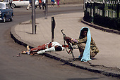 Addis Ababa, Ethiopia<br /> May 30, 1991<br /> <br /> A demonstrator opposing the new government was shot and left in the street for public display. He is guarded by a member for the new military rebels.<br /> <br /> In late May 1991 the long civil war in Ethiopia came to a climax when the alliance of four rebel groups, the Ethiopian People's Revolutionary Democratic Front (EPRDF), toppled the authoritarian government of Mengistu Haile-Mariam and took control of Addis Ababa and the nation. The governing regime declared a cease-fire and fled. In July 1991 the 24 different groups met in the capital and established a multi-party provisional government headed by Meles Zenawi,  the Tigray Rebel Leader, to lead the country to its first free elections within two years.