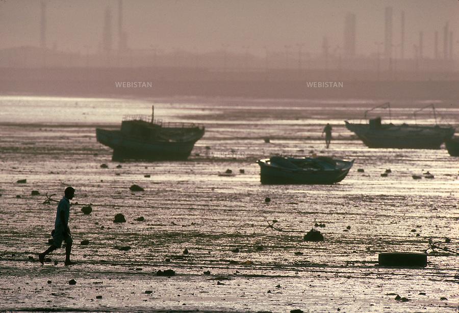..Egypt. Suez. 1996. In the harbour bay, Egyptian fishermen wait for the tide to come in to reach their boat...Egypte. Suez. 1996. Dans la baie du port, des pecheurs egyptiens attendent la montee de la maree pour rejoindre leurs bateaux.