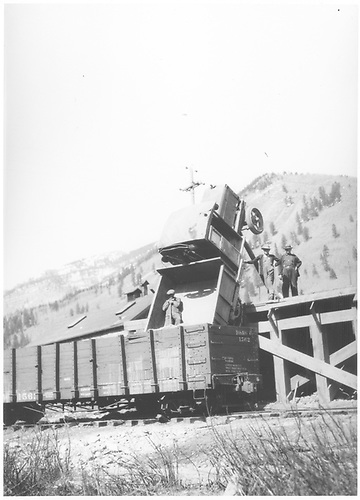 View of the St. Louis Tunnel Loading Dock with D&amp;RGW gondola #1562 spotted in front.  A half-track truck has backed off the dock into the gondola with truck positioned vertically and resting on its tail gate.  Three workmen with shovels are posing in this scene.<br /> RGS  Rico, CO