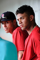 Second baseman Yoan Moncada (24) of the Greenville Drive, right, talks to the media before a game against the Lexington Legends on Monday, May 18, 2015, at Fluor Field at the West End in Greenville, South Carolina. Moncada, a 19-year-old prospect from Cuba, made his professional debut tonight in the Red Sox organization. On Moncada's right is Laz Gutierrez, who was interpreting for the Spanish-speaking ballplayer. (Tom Priddy/Four Seam Images)
