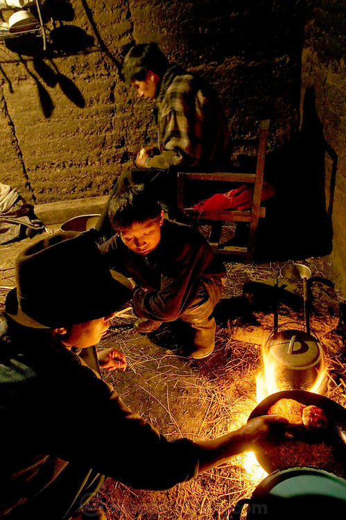 (MODEL RELEASED IMAGE) Ermelinda Ayme cooks empanadas for her children in the family's earthen kitchen house as one of her sons watches. Husband Orlando slices onions to help his wife, an unusual task for a village man to undertake in Ecuador. (From a photographic gallery of kitchen images, in Hungry Planet: What the World Eats, p. 55)